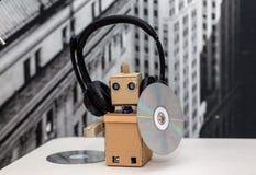 Roboter in den Kopfhörern, die in handsa Musik CD halten Stockfotos