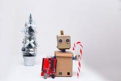 Roboter, der Chip und Dekoration des neuen Jahres hält Stockbild