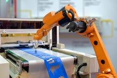 Roboter, der ein Werkstück aus der Maschine heraus greift Stockbild