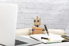 Roboter, der an einem Schreibtisch arbeitet der Arbeitsprozeß stockbilder