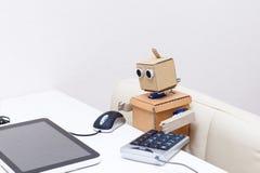 Roboter, der an einer Tastatur am Tisch arbeitet Stockfotografie