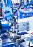 Roboter, der Kleberspritze Einspritzung am Telefon hält Lizenzfreies Stockbild