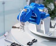 Roboter, der Kleberspritze Einspritzung am Telefon hält Stockbild