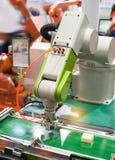 Roboter, der Kleberspritze Einspritzung am Telefon hält Stockfoto