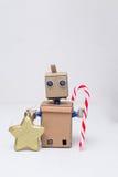Roboter, der Weihnachtsdekorationen auf dem weißen Hintergrund hält Stockfoto