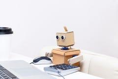 Roboter, der zu Hause an einem Laptop am Tisch arbeitet Stockfotos