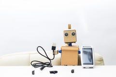 Roboter hält eine Solarbatterie in seiner Hand, in der anderen Hand ein wir Stockbilder
