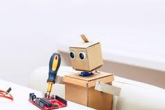 Roboter macht Chip und sitzt auf einem Stuhl am Tisch Stockfoto