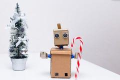 Roboter mit den Armen und den Weihnachtsdekorationen auf dem Tisch Stockbilder
