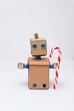 Roboter mit den Händen, die einen Lutscher für Weihnachten halten Neues Jahr Stockfotos