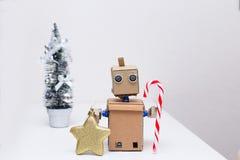 Roboter mit den Händen, die einen Lutscher für Weihnachten halten Neues Jahr Lizenzfreie Stockbilder