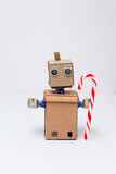 Roboter mit den Händen, die einen Lutscher für Weihnachten halten Neues Jahr Lizenzfreies Stockfoto