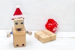 Roboter mit den Händen in einem Weihnachtshut und in einer Geschenkbox Lizenzfreie Stockbilder