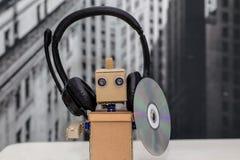 Roboter mit Kopfhörern und dem Halten einer Diskette Lizenzfreies Stockbild