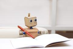 Roboter schreibt das Sitzen am weißen Tisch in Schreiben Lizenzfreie Stockfotografie