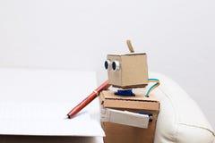 Roboter schreibt einen Stift in ein Notizbuch am Tisch Stockbild
