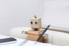 Roboter schreibt einen Stift in ein Notizbuch am Tisch Lizenzfreie Stockfotografie