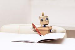 Roboter schreibt mit einem Kugelschreiber und dem Sitzen am Tisch Lizenzfreie Stockfotos