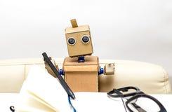 Roboter sitzt auf einem Stuhl an einer Schreibtischleuchte Stockbild