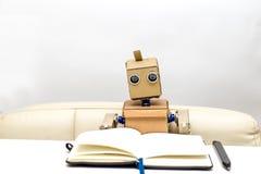 Roboter sitzt an einem Tisch auf einem hellen Hintergrund, Stockfoto
