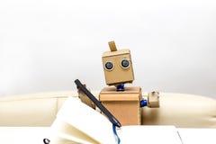 Roboter sitzt am Leuchtpult auf einem hellen Hintergrund Lizenzfreie Stockfotografie