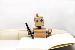 Roboter sitzt am Tisch Lizenzfreies Stockfoto