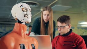 Roboter wird hergestellt, um zu blinzeln von einem Mann und weibliche Spezialisten mittels eines Computers stock video footage