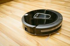 RoboterStaubsauger auf lamellenförmig angeordnetem Holzfußboden lizenzfreie stockfotos
