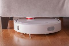 Roboterstaubsauger läuft unter Sofa im Raum auf Laminatboden Roboter gesteuert durch Sprachsteuerungen, Reinigung zu verweisen Mo Lizenzfreie Stockfotos