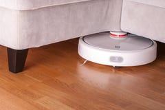 Roboterstaubsauger läuft unter Sofa im Raum auf Reinigungstechnologiehaushaltung des Laminatbodens moderner intelligenter stockbilder