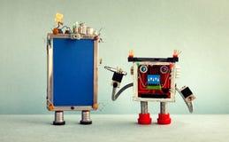 Robotfaktotum och bruten smartphone Robotmilit?ren med en skruvmejsel ?nskar att fixa telefonen fotografering för bildbyråer