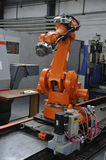Robotic Arm. Orange robotic arm in factory hall royalty free stock photo