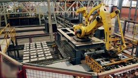 Robotic arm at factory floor sorts bricks on a conveyor. stock footage