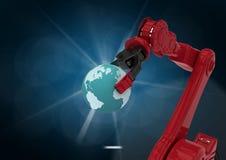 Robotic arm holding globe against blue background Stock Photo