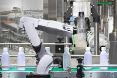Robotic arm holding water bottles on drink production line royalty free stock images