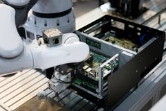 Robotic arm installing a computer chip in factory. Industrial an. D factory with machine technology 4.0 concept stock images
