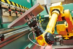 Robotics in hydraulic press brake or bending machine for sheet metal. Robotic arm moving metal sheet at hydraulic press brake or bending machine stock images
