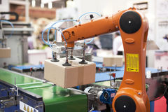 Robotic arm. Packaging line with robotic arm at work royalty free stock photography