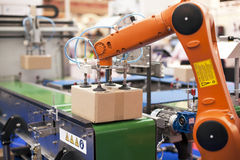 Robotic arm for packing. Packaging line with robotic arm at work stock images