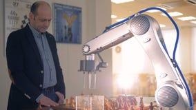 Robotic arm som spelar schack med en yrkesmässig schackspelare stock video