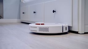 A robotic vacuum lightly connects with rooms furniture. stock video