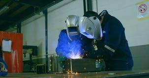 Robotic engineers welding metal in robotic warehouse 4k stock video footage