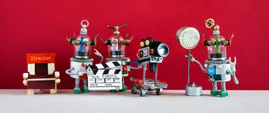 Robotic filmmaking. Talented robots shoots television movie or motion picture. Creative filmmakers robotic crew director. Assistant with spotlight and stock image