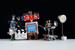 Robotic filmskaparekameraman, assistent med clapperboard bak platsfilmrobotarna Automatiserad video film royaltyfri bild