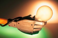 Robotic Hand Holding Lightbulb Stock Image