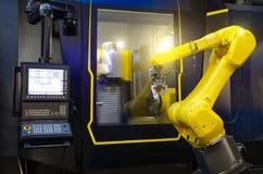 Robotic handmaskinhjälpmedel på den industriella tillverkningfabriken som arbetar i samverkan med en numeriskt kontrollerad maski Arkivbild