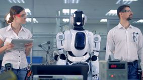 Robotic humanoid is turning its head after a male engineer. 4K stock footage