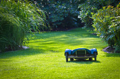 Robotic Lawn Helper. Photograph of a robotic lawn mower, working the garden Royalty Free Stock Images