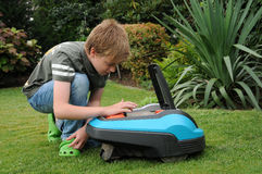 Robotic lawn mower. Teenager boy keys in the code number and started robotic lawn mover royalty free stock photos