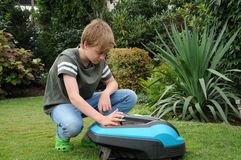 Robotic lawn mower. Teenager boy keys in the code number and started robotic lawn mover royalty free stock images